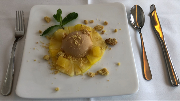 Dome of white chocolate on curried Pineapple Carpaccio and Crumbles